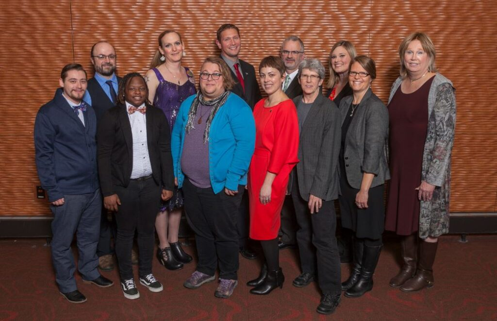 A group of people stand together posing for a group photograph.