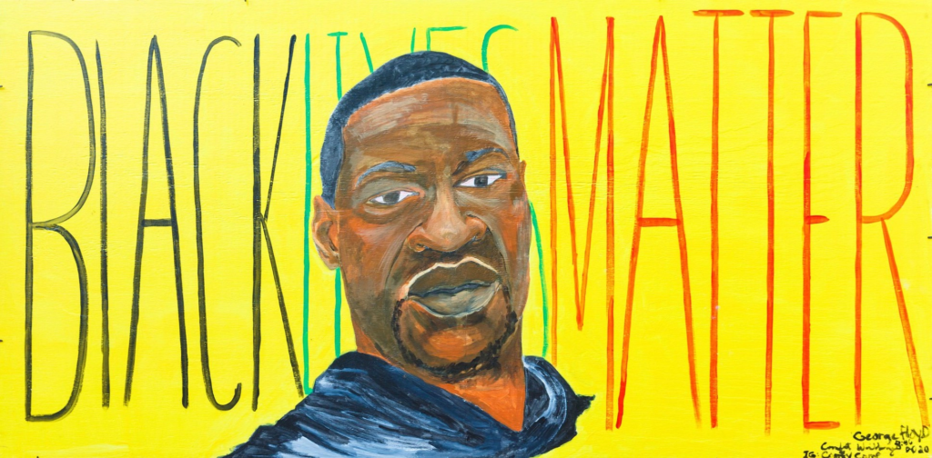 """A mural with a yellow background and a painting of George Floyd with the words """"Black Lives Matter"""" written behind his head in black, green and red lettering."""