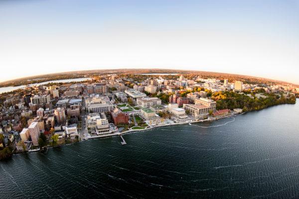 fish-eye aerial shot of campus from over Lake Mendota