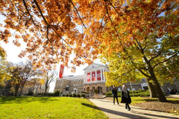 People walking among bright orange fall leaves on Bascom hill with Bascom Hall in the background.