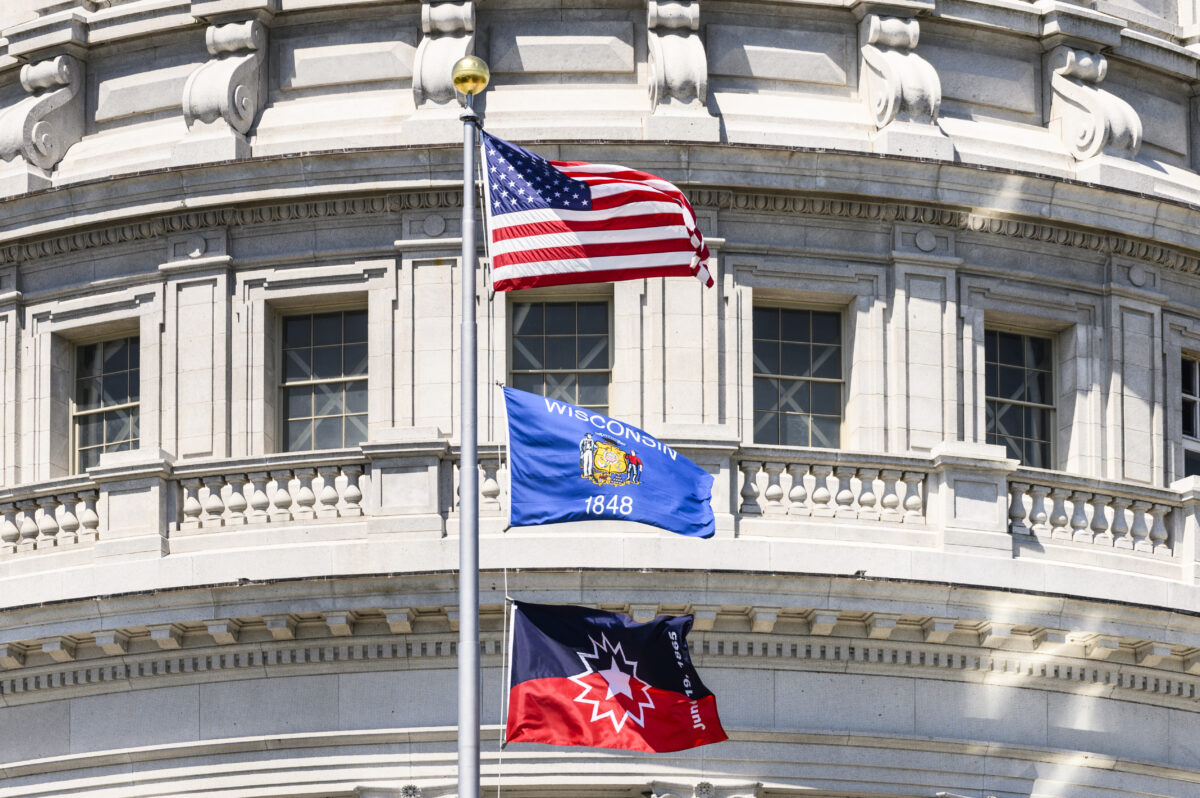 The Juneteenth flag is flown below the Wisconsin flag and American flag on a pole in front of the Wisconsin Capitol building.