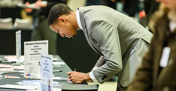 A student fills out a name tag before meeting with company representatives at a job fair.
