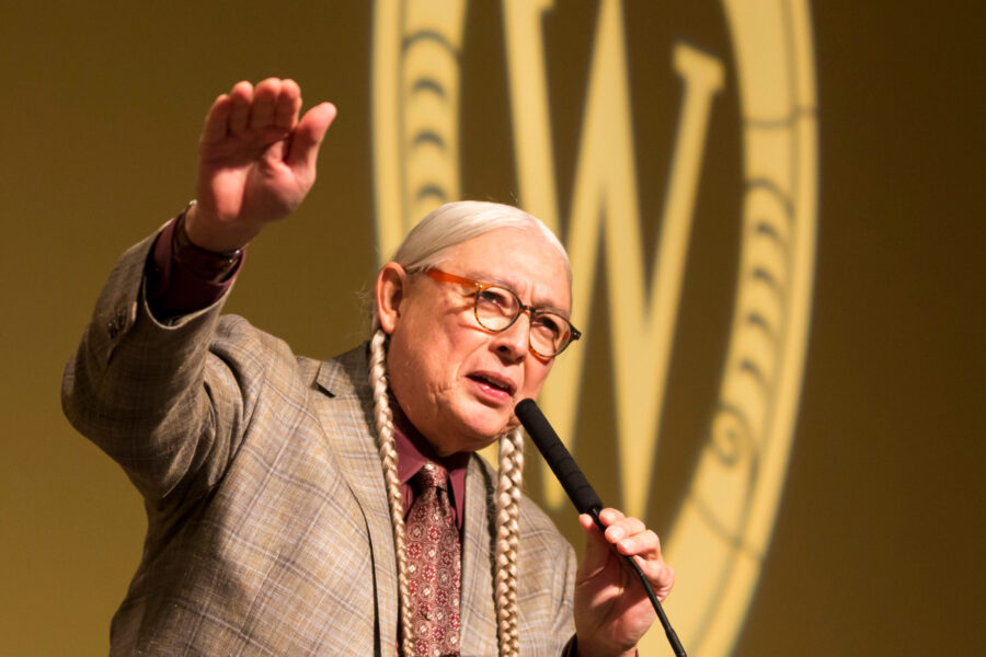 Walter Echo-Hawk gestures and speaks into a microphone at a podium