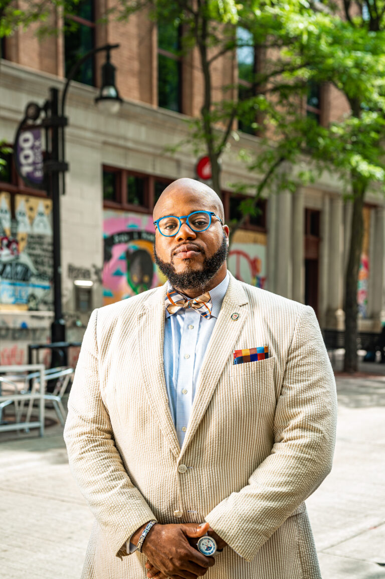 Portrait of LaVar Charleston wearing a white suit and colorful bowtie standing on State Street