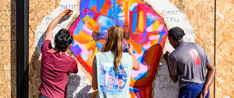 Three students paint a colorful mural of a fist with names around it